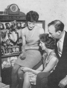 1966 Gloria Dourass at home with parents and trophies MBM-Wi66P32.jpg