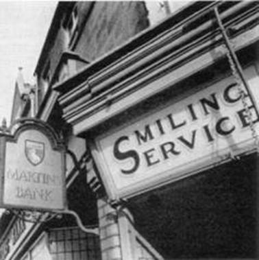 1958 Exterior showing sign only and smiling service sign on shop next door MBM-Wi58P24.jpg